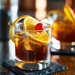 tasty alcoholic old fashioned cocktail with orange slice, cherry, and lemon peel garnish shot with selective focus
